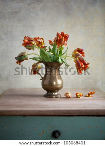 Ornamental orangey-yellow tulips in an antique metal jug with fallen petals on the old wooden tabletop