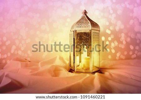 Ornamental silver Moroccan, Arabic lantern on linen throw. Burning candle, glittering colorful bokeh lights. Greeting card for Muslim community holy month Ramadan Kareem. Festive background. #1091460221