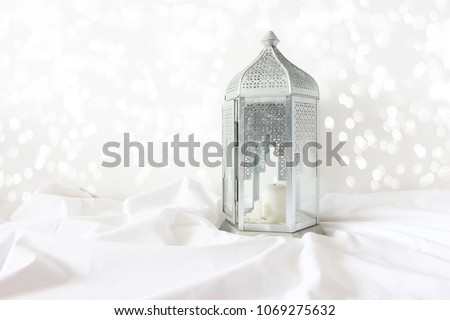 Ornamental silver Moroccan, Arabic lantern on white linen throw. Burning candle, glittering bokeh lights. Greeting card for Muslim community holy month Ramadan Kareem. Festive background. #1069275632