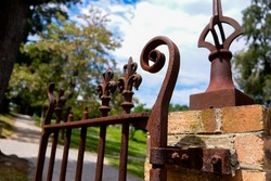Ornate and weathered wrought iron fence affixed to orange yellow gate posts