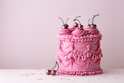 Ornate birthday cake with vintage style buttercream ruffles and cherries