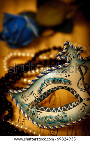 Ornate carnival mask on a music paper with rose and pearls