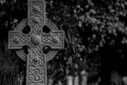 Ornate Celtic cross in black and white. Dark scene.