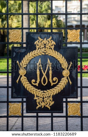 Ornate decoration of fence with artistic monogram, letter M #1183220689