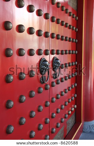 Ornate doorways to traditional chinese temple with guardian door knockers