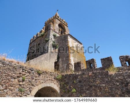 Ornate entrance, with bell tower, Porta da Vila known as Village Door or Porta Nova, close up. Remains of ancient castle or Castelo de Montemor-o-Novo and stone masonry wall ruins. Foto stock ©