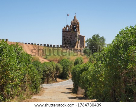 Ornate entrance, with bell tower, Porta da Vila known as Village Door or Porta Nova visible in the distance. Remains of ancient castle or Castelo de Montemor-o-Novo and stone masonry wall ruins. Foto stock ©