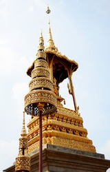 Ornate golden monument detail (busabok) with royal insignia showing a thai crown in the Grand Palace complex, Bangkok, Thailand