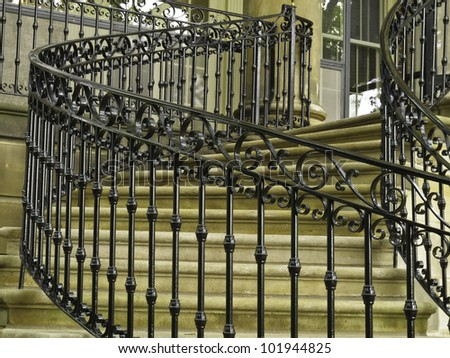 Ornate handrail of wrought iron along curved staircase to main entrance of public museum stock for Curved metal railings exterior