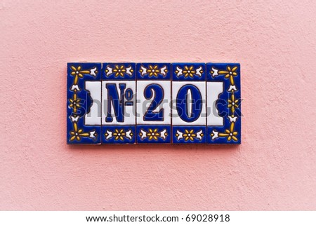 Ornate house number tiles on a pink wall, subtle white vignette adds impact