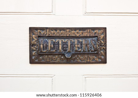 Ornate letterbox in a white wooden door