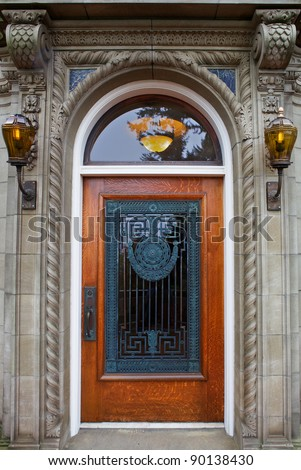 Ornate stained Wood Door with unique old bronze facing between Two Lanterns