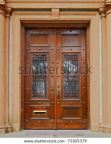 Ornate stained wood doors with wrought iron grating over glass windows