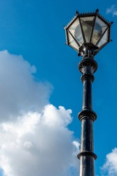 Ornate street lamp and post made of iron metal captured against blue sky and white clouds. Perspective view from ground level.
