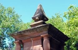 Ornate 19th Century Classical Style Stone Gate Post seen from Below against Blue Sky