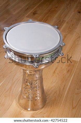 Ornate turkish silver drum on a wooden floor