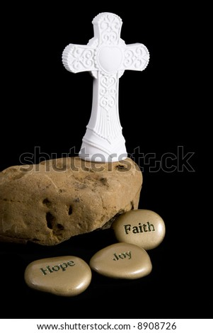 "Ornate white cross standing on a rock.  Inspirational stones that read ""Faith"", ""Hope"", and ""Joy"".  Isolated on black."