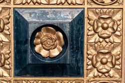 Ornately decorated gold panels adorned with embossed flower designs and dominated by a black raised panel featuring a contrasting centrally located gold flower motif.