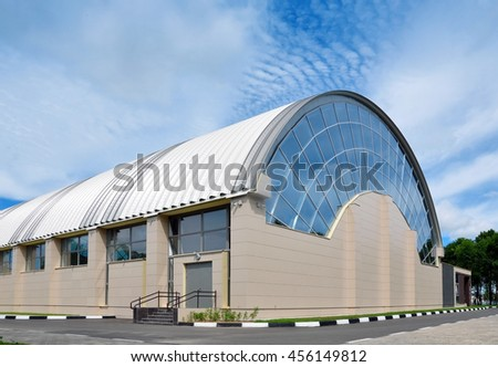 Orsha, Belarus - July 16, 2016: Sport Complex in Orsha. Facade of modern building of circular shape. The design of arched ribbed roof and wall with glass and sandwich panels. #456149812