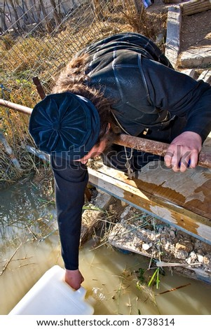 Orthodox Christian filling a bottle with Jordan river Holy Water, Jesus Baptism site, Israel