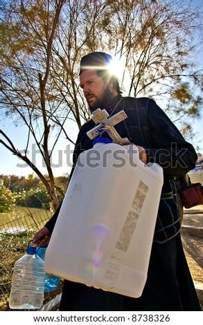 Orthodox Christian filling a bottle with Jordan river Holy Water, Jesus Baptism site, Israel