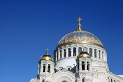 Orthodox Church in Kronstadt and blue sky. Golden and white domes of the russian church with saturated blue sky. Nicholas sea cathedral in a sunny day.