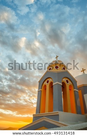Orthodox church in rays of beautiful sunset. Fira, Santorini Greece. Copyspace #493131418