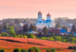 Orthodox Church in the village of Kolyvan in the pink light in the morning haze