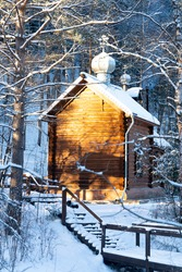 Orthodox Church in the winter in the forest. Snow-covered staircase leading to the church. Beautiful forest landscape. Church - side view.