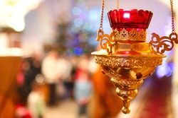 Orthodox church lamp with a lighted candle and red glass on the background of an Orthodox icon and a blurred reflection of the Christmas tree, Orthodoxy. The concept of Orthodoxy.