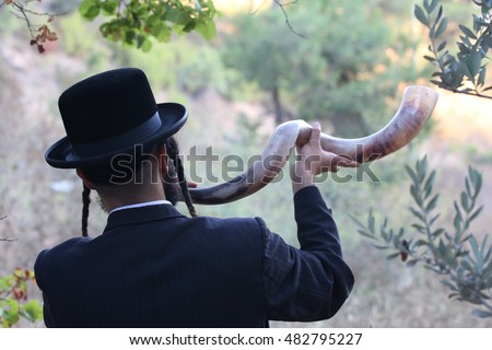 orthodox Jew blowing the shofar of Rosh Hashanah.\ indistinct man in background blur blows a long yemenite shofar horn with focus on the open end of the horn; isolation on forest.