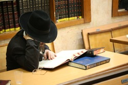 Orthodox Jew Studying Torah . Special character of the Jewish rabbi, with a white beard and black hat