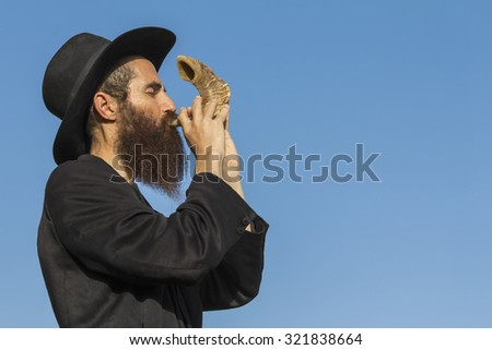 Orthodox Jewish man blast in Shofar at Rosh Hashana holiday on blue sky background