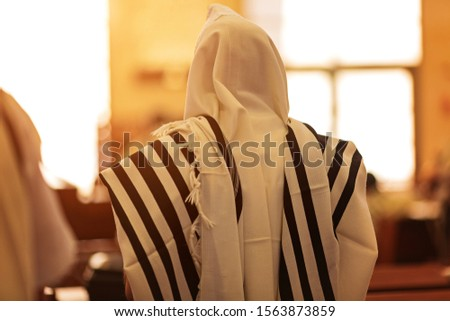 Photo of  Orthodox ultra Orthodox Jew from a tallit in the synagogue. rear view of an orthodox Jew in the mantle, a bit in the synagogue