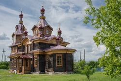 Orthodox wooden temple in the Siberian outback. Green grass and blue sky. The village of Bolshoy Balchug is located on the banks of the Yenisei river, 100 km from Krasnoyarsk.