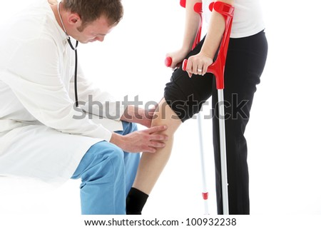 Orthopaedic surgeon examining woman's knee Orthopaedic surgeon sitting examining the knee of a female patient on crutches following surgery for a joint injury