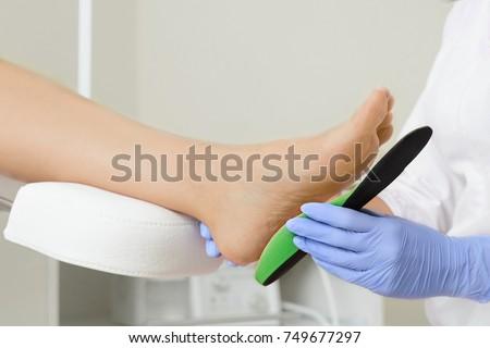 Orthopedic insoles. Fitting orthotic insoles. Flatfoot treatment. Podiatry clinic.  Stockfoto ©