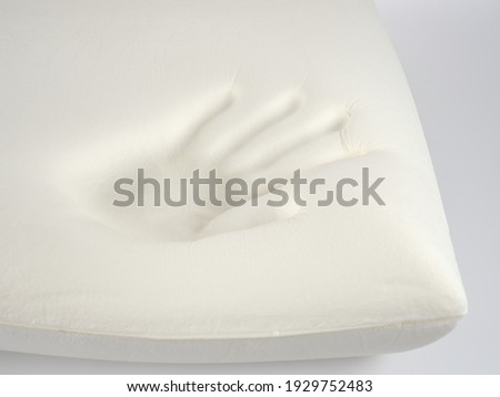 Orthopedic pillow, memory foam. Handprint on the pillow. Comfortable bedding with orthopaedic, therapeutic effect. Memory foam material.