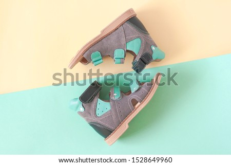 Orthopedic shoes for kids on a yellow and green background. Top view #1528649960