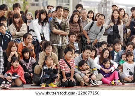 OSAKA, JAPAN, NOVEMBER 13, 2011: Japanese public crowd is watching a magician show performed at the aquarium square in Osaka, Japan #228877150