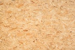 OSB boards are made of brown wood chips sanded into a wooden background. Top view of OSB wood veneer background, tight, seamless surfaces.