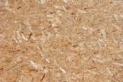 OSB (oriented strand board), rough surface of chipboard recycled wood made by compressing tiny piece of wood strands (flakes), wooden fragment abstract pattern background