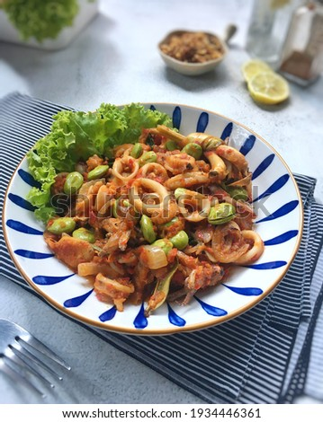 Oseng cumi petai pedas or cumi petai mercon or spicy squid with stink bean is indonesian traditional food. It cooked with red chilli, gosh pepper, spices and bitter bean or stink bean. Selective focus Stock fotó ©