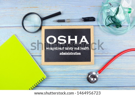 Osha, Occupational Safety and Health Administration. Blackboard on a wooden background.