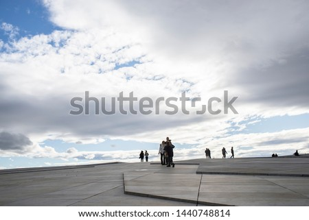 Oslo, Norway - 8/10/2018: the modern architecture of the Oslo Opera House in Oslo, Norway. Tourists walk on the marbled paving that surrounds the opera house.People walk on the plateau of the opera .