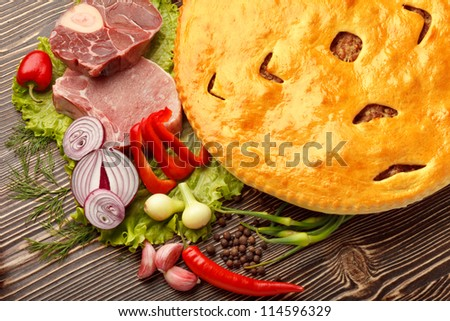 Ossetian cuisine. Fydzhin meat pie and vegetables on wood.