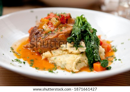 osso buco hand made with polenta and a tomato sauce with fresh greens Foto stock ©