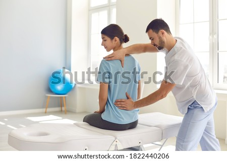 Osteopathic medicine and physiotherapy. Licensed osteopath examining young woman in modern hospital office. Chiropractor helping female patient with scoliosis, low back pain or other spine problems