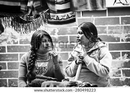 OTAVALO, ECUADOR - JAN 3, 2015: Unidentified Ecuadorian girls work at the Otavalo Market. 71,9% of Ecuadorian people belong to the Mestizo ethnic group