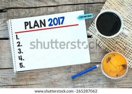 Otebook with plan 2017. Notebook with plan 2017 and sticker remember on wooden desk with cup of coffee and muffin